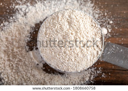 Einkorn siyez whole wheat flour in metal measuring cup on natural background. #1808660758