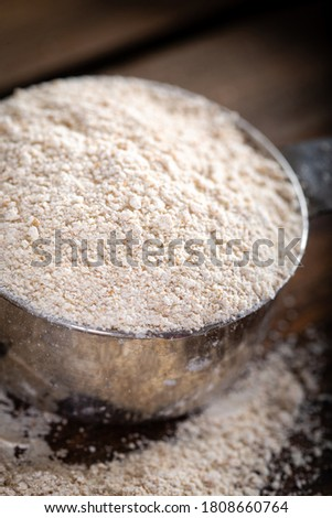 Einkorn siyez whole wheat flour in metal measuring cup on natural background. #1808660764