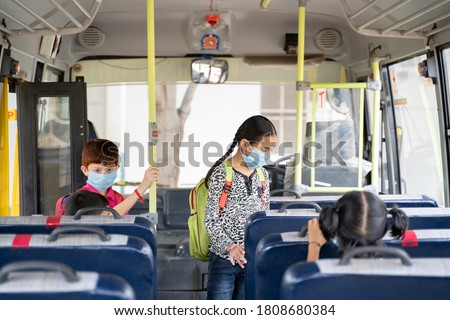 Kids with medical mask coming inside school bus and sitting on seats while maintaining social distance due to coronavirus or covid-19 pandemic - Concept of school reopen or back to school. Royalty-Free Stock Photo #1808680384
