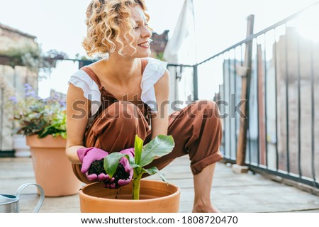 Pleasant active resting terrace. Blond romantic female gardener in overalls enjoying hobbie, creating garden at balcony. Plants cultivation and nursery, garden maintenance. Royalty-Free Stock Photo #1808720470