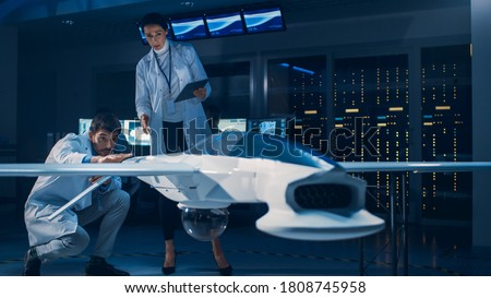 Meeting of Aerospace Engineers Working On Unmanned Aerial Vehicle / Drone Prototype. Aviation Scientists in White Coats Talking. Commercial Aerial Surveillance Aircraft in Industrial Laboratory #1808745958