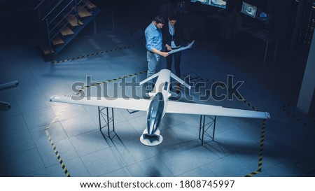 Meeting of Aerospace Engineers Work On Unmanned Aerial Vehicle / Drone Prototype. Aviation Experts have Discussion. Industrial Facility with Aircraft Capable of GPS Surveillance and Military Missions Royalty-Free Stock Photo #1808745997