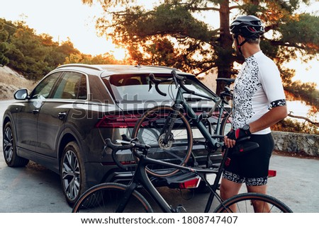 Male cyclist loading his bicycle on a rack of his crossover car Royalty-Free Stock Photo #1808747407