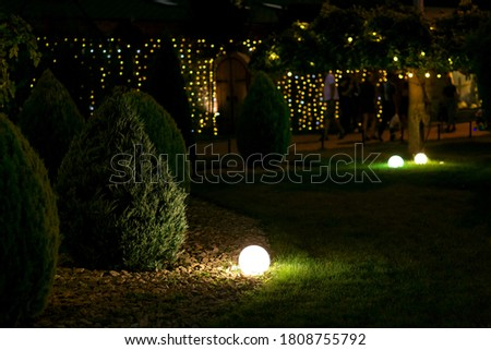 illumination landscape light park with electric ground lantern with round diffuser lamp with garland of light bulbs on background, dark landscaping with illuminate night scene. Royalty-Free Stock Photo #1808755792