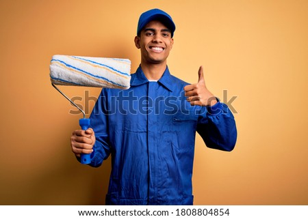 Young handsome african american painter man wearing uniform using painting roller happy with big smile doing ok sign, thumb up with fingers, excellent sign