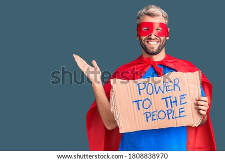 Young blond man wearing super hero custome holding power to the people cardboard banner celebrating victory with happy smile and winner expression with raised hands