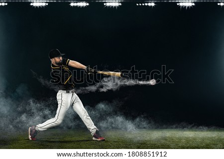 Baseball player with bat taking a swing on grand arena. Ballplayer on dark background in action. Royalty-Free Stock Photo #1808851912