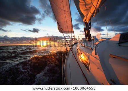Yacht sailing in an open sea at sunset. Close-up view of the deck, mast and sails. Clear sky after the rain, dramatic glowing clouds, golden sunlight, waves and water splashes, cyclone. Epic seascape Royalty-Free Stock Photo #1808864653