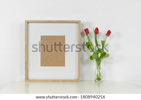 Close up view of an empty picture frame, with red tulips placed in a glass vase arranged on a plain white background
