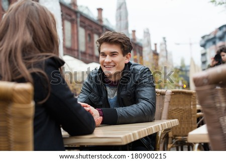 Happy young man with woman at outdoor restaurant #180900215