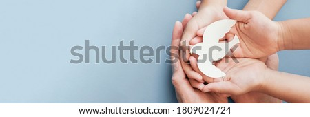 Adult and child hands holding white dove bird on blue background, international day of peace or world peace day concept, sustainable consumption, csr responsible business concept Royalty-Free Stock Photo #1809024724