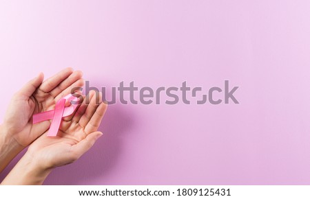 Healthcare and breast cancer awareness concept. Hands holding pink ribbons, Breast cancer awareness, symbolic bow color raising awareness on women's breast tumor. #1809125431
