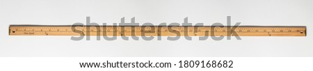 Wooden yardstick on white backgrounds whit inches and yard fractions scales. Royalty-Free Stock Photo #1809168682