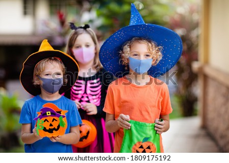 Kids trick or treat in Halloween costume and face mask. Children in dress up with candy bucket in coronavirus pandemic. Little boy and girl trick or treating with pumpkin lantern. Autumn holiday fun. #1809175192
