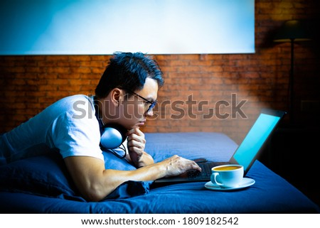 young asian man staring at laptop computer screen in bedroom at night. eye problems concept Royalty-Free Stock Photo #1809182542