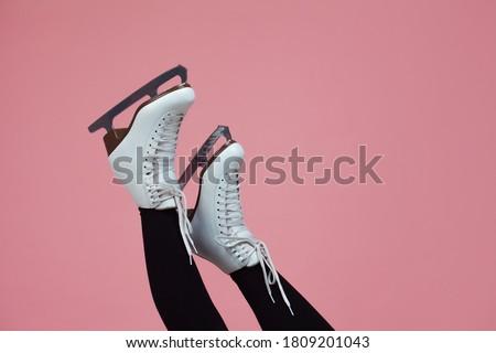 Figure skating is a winter sport and leisure. Women's feet in ice dancing skates. Slender female legs in white skates for figure skating.