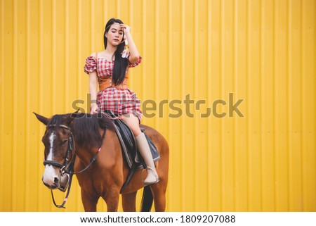 A beautiful Asian woman wearing a red checkered dress She is riding a brown horse. With a yellow background