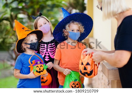 Kids trick or treat in Halloween costume and face mask. Children in dress up with candy bucket in coronavirus pandemic. Little boy and girl trick or treating with pumpkin lantern. Autumn holiday fun. #1809210709