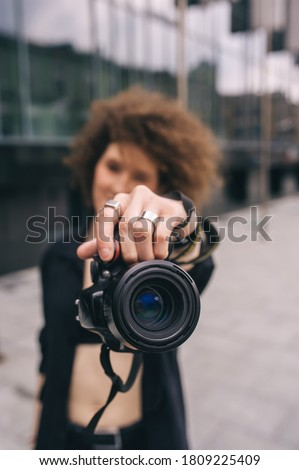 Photographer woman taking a photo with digital 50mm lens reflex camera. Young curly girl taking photo of you with mirror camera. Photographer with lens in hand on city street. Focus on lens
