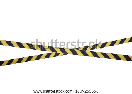 Black and yellow lines of barrier tape prohibit passage. Barrier tape on white isolate. Barrier that prohibits traffic. Warning tape. Danger unsafe area warning do not enter. Concept of no entry Royalty-Free Stock Photo #1809255556