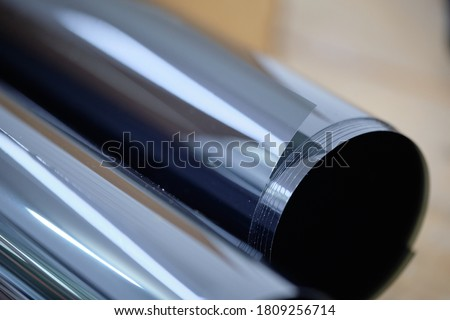 Close up of car window tint. Ceramic film provide heat rejection & UV protection. Roll of automobile film before installed to glass surface. Professional tinting service background. #1809256714