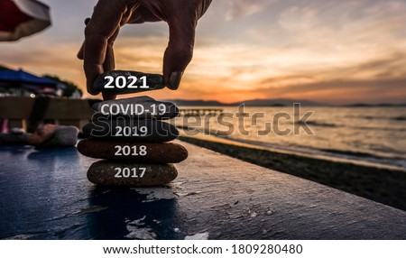 New Year 2021 is coming concept. Covid year 2020 to 2021 background. Positive turn of old year. Happy new year 2021 replace corona. New hopes, excitement with 2021. Man adding stone to pebble tower #1809280480