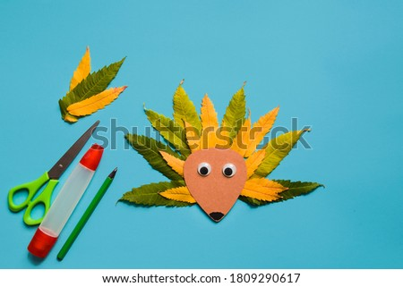 little child making autumn decoration from leaves. Children's art project. DIY concept. Step-by-step photo instruction.