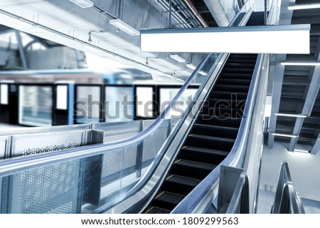 Blank sign board in subway train station with escalator background. It is direction signage mock up for information public transport. Tourists traveling by metro train to get to tourist attractions.