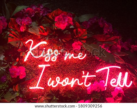 Pink neon sign that says Kiss me I won't tell with flower decor