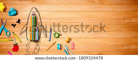 Back to school theme with a rocket with school supplies Royalty-Free Stock Photo #1809324478