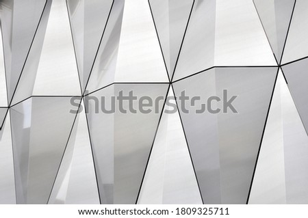 Mirror surface of stainless steel with crystals in the wall, decor and reflection. Abstract glass background. Polygonal surface. Close-up.