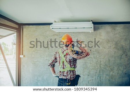 Portrait  air conditioner technician or air-conditioning installation technician is about to repair air conditioning in homes and buildings.Air conditioner repairmen work on home unit. Royalty-Free Stock Photo #1809345394