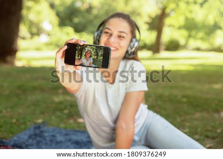 Young beautiful woman taking selfie with her smartphone in the park while she listening the music over wireless headphones