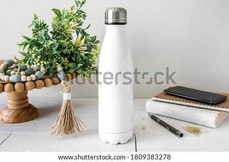 Blank white steel insulated water bottle on white background with rustic neutral props, double walled drinkware mockup