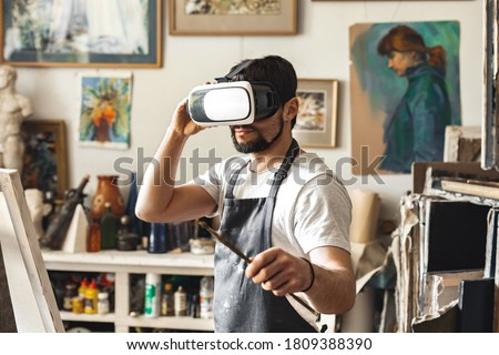 Young male painter standing at art studio indoors wearing virtual reality headset checking picture online holding brush smiling curious