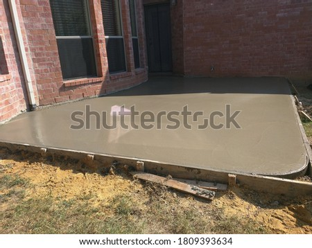 Ready-mixed concrete poured after placing steel reinforcement to make a patio in a backyard