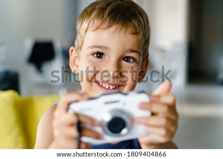 Close up portrait of happy small boy holding digital camera taking photo while sitting on the sofa at home in summer day - domestic life leisure and growing up concept