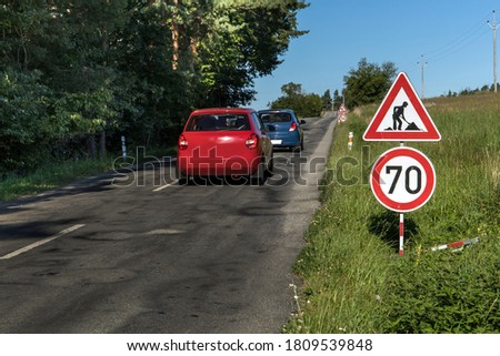 Roadworks signs on a Country Road and Blue Sky. Summer morning on a country road in the Czech Republic. Road repair. Road sign.