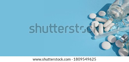 white pills are sprinkled on a blue background. in a transparent jar white pills near ampoules. banner with place for text in the middle and on the left. view from above