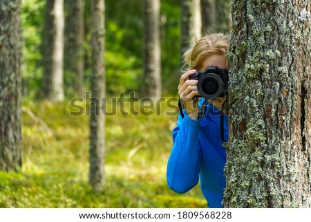 Young woman trekking among trees and taking pictures with camera. middle age woman photographer taking picture in autumn forest. Nature photography.