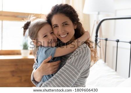 Portrait of loving mum hug little daughter sit in bed feels happy spend time together. Carefree motherhood, new mom for grateful adopted kid, good morning, fun at home, Mother or Child day celebration