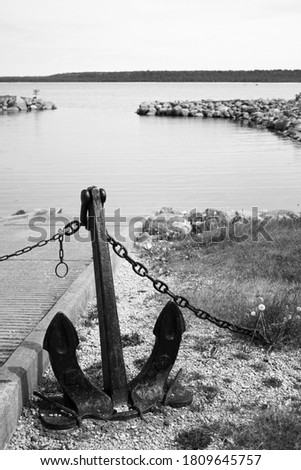 Anchor resting at port. Black and white picture of an anchor by the seaside.