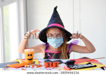A little girl in a witch costume in a medical mask makes crafts and scares. Halloween with safety measures from Covid-19 #1809646156