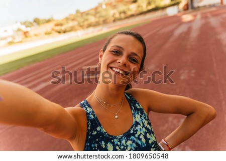 Young girl with brown hair smiling and taking a picture with her mobile phone during training session on the running track