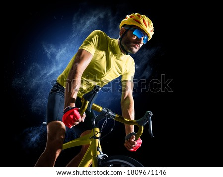 Professional road bicycle racer in action isoated on the black background Royalty-Free Stock Photo #1809671146