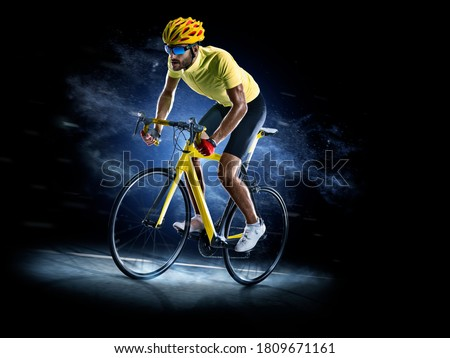 Professional road bicycle racer in action isoated on the black background Royalty-Free Stock Photo #1809671161