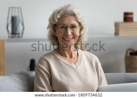 Head shot portrait smiling beautiful mature woman wearing glasses looking at camera, sitting on cozy couch at home, positive happy middle aged female posing for photo in living room
