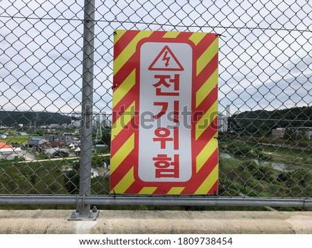 Safety signs are in Korean, meaning 'electrical hazard'. Danger high voltage.