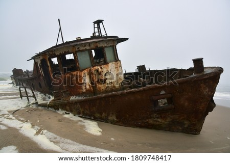 Wreck of a trawler that ran aground in 1976 on the beach off the Atlantic Ocean in the Namib Desert Royalty-Free Stock Photo #1809748417