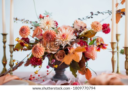 Beautiful flower composition with autumn orange and red flowers and berries. Autumn bouquet in vintage vase on a wooden table with pink tissue and candles #1809770794